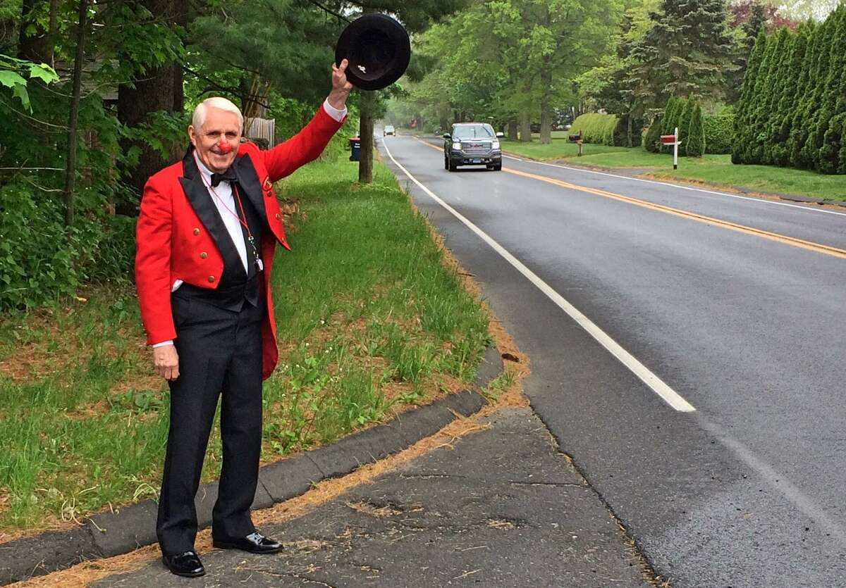Trumbull resident William Murphy, wearing his 1992 Barnum Festival Ringmaster attire, waves to passing traffic at noon on Memorial Day during the town's one-minute noise salute to veterans and emergency responders.
