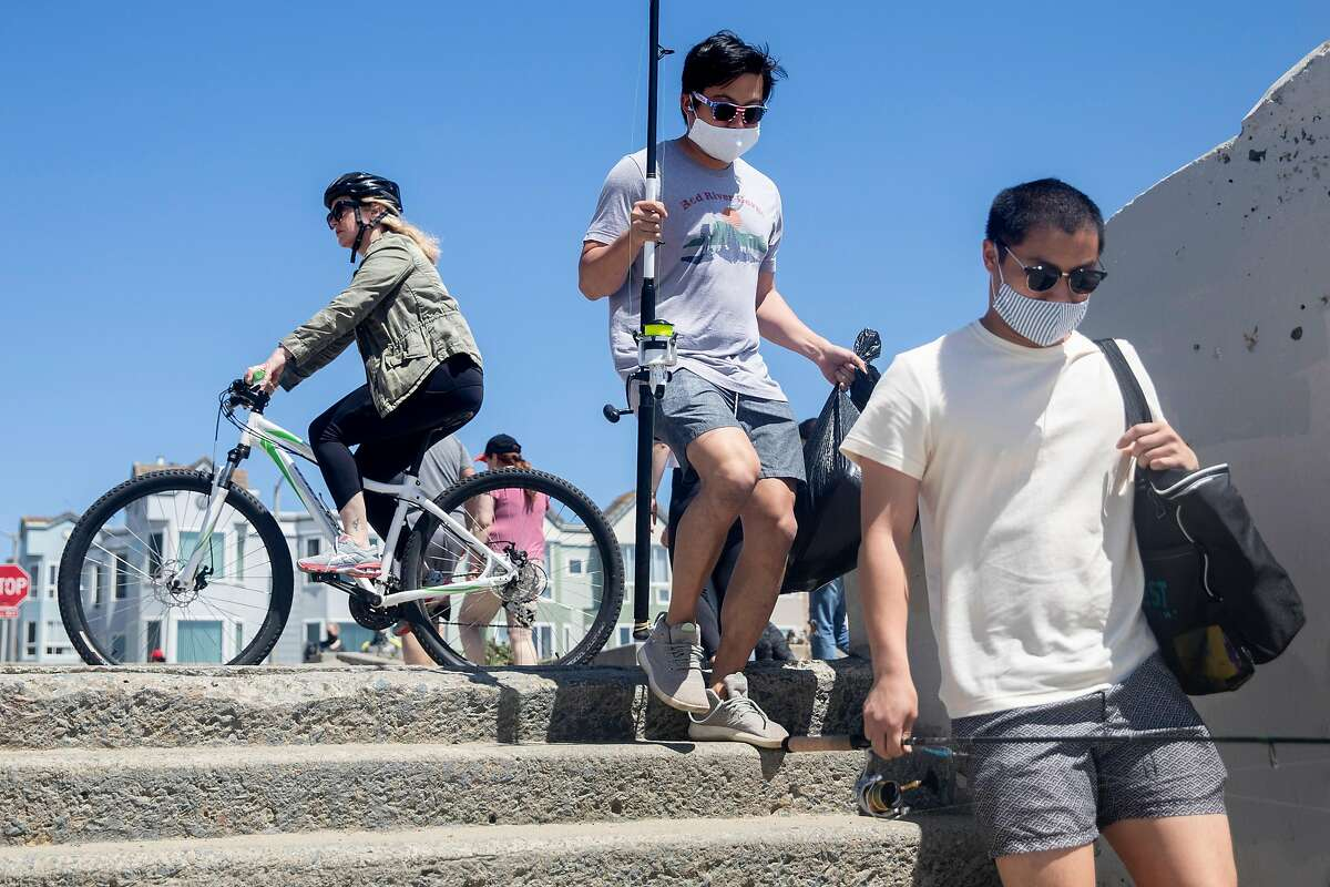 Two people sport masks while waking down the steps to Ocean Beach in San Francisco, Calif. Monday, May 25, 2020. The warm Memorial Day weather brought out large crowds to popular parks and beaches despite the shelter-in-place order amid the COVID-19 pandemic.