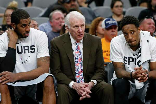 Spurs coach Gregg Popovich head coach talks with players LaMarcus Aldridge, left, and DeMar DeRozan on the bench during a game against the Houston Rockets on Nov. 30, 2018 at the AT&T Center in San Antonio.