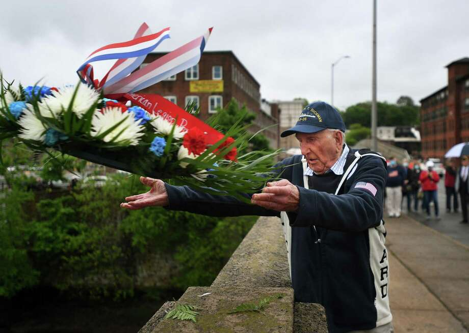 World War II veteran Jay Eugster, 98, of Shelton, throws a wreath into the Housatonic River from the Derby-Shelton Bridge during the annual Memorial Day ceremony in Shelton on Monday. Photo: Brian A. Pounds / Hearst Connecticut Media / Connecticut Post