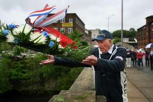 World War II veteran Jay Eugster, 98, of Shelton, throws a wreath into the Housatonic River from the Derby-Shelton Bridge during the annual Memorial Day ceremony in Shelton on Monday.
