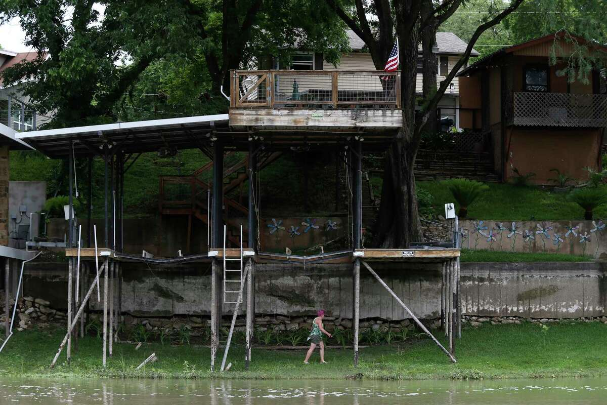 A woman picks up debris under a boat dock at Lake Dunlap, Monday, May 25, 2020. The dam that created the lake was built in 1931 to provide hydroelectric power. It failed on May 14, 2019 and the lake drained leaving only the natural path of the Guadalupe River.