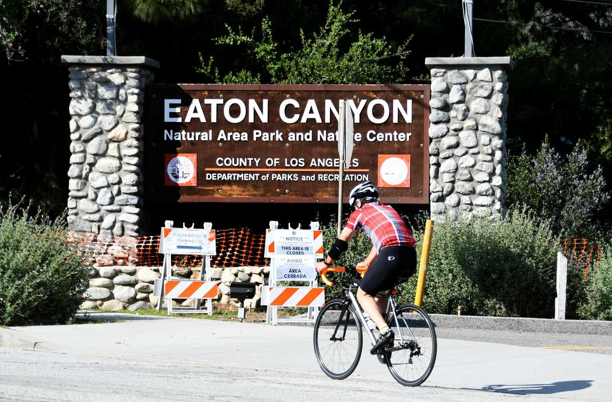 A cyclist rides past the closed Eaton Canyon Natural Area Park in Altadena on April 14, 2020.