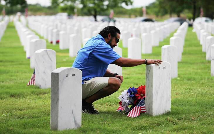 Raymundo Soto visits the gravesite of Lt. Col. Albert E. Smart with whom Soto served with in 321st Civil Affair Brigde as people visit Fort Sam Houston National Cemetery on Memorial Day to pay their respects on Monday, May 25, 2020. Soto makes a visit every year.