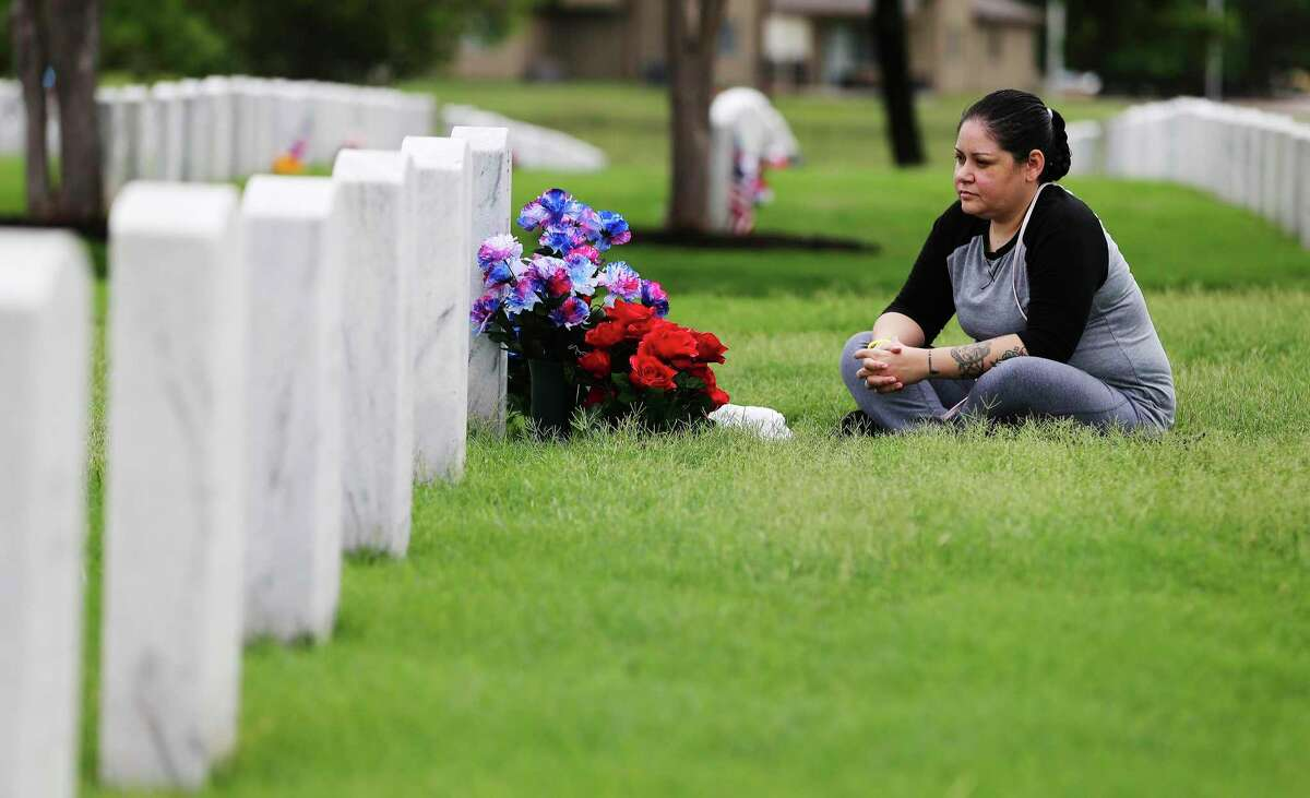 Ret. Army Spc. Irene Brown sits beside the grave site of her husband, Army Spc. Losse Keone Brown, on Monday.