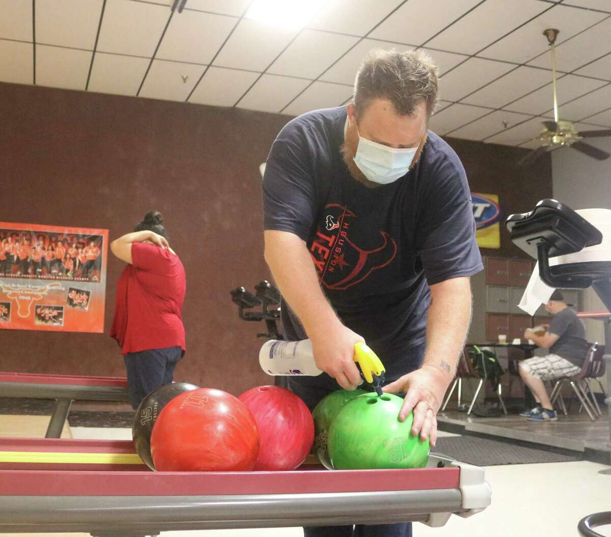 Armadilla Lanes employee Darrin Williams sprays disinfectant inside the finger holes of a ball Monday afternoon as the facility celebrated its long-awaited reopening.