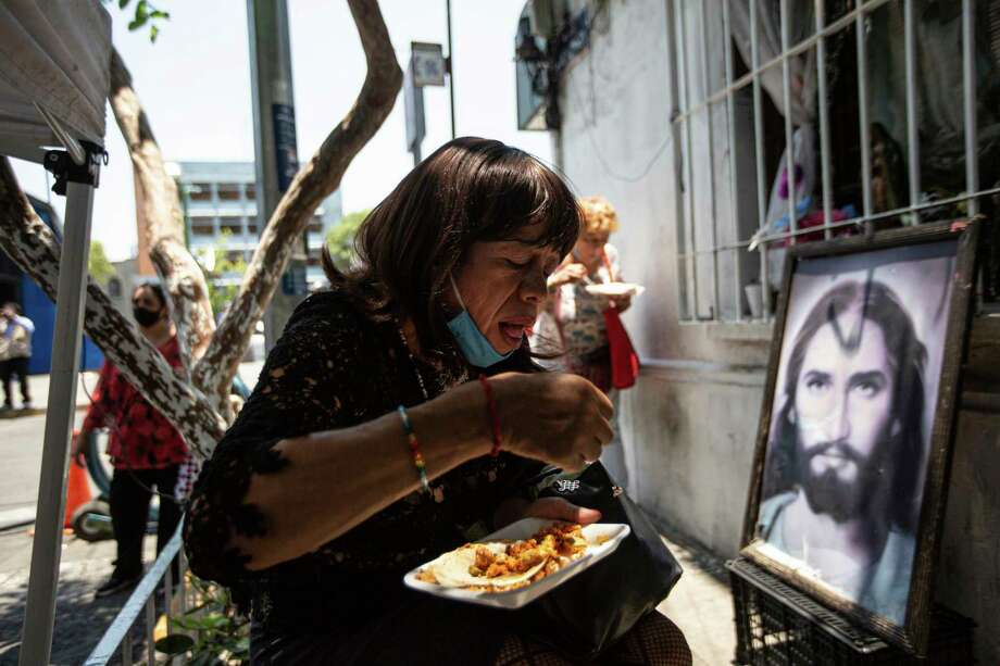 A woman eats a free meal beside a framed image of Jesus Christ during a program created by LGTB activists for people who have not been able to work because of the COVID-19 pandemic in Mexico City, Monday, May 25, 2020. Photo: Fernando Llano, AP / Copyright 2020 The Associated Press. All rights reserved.