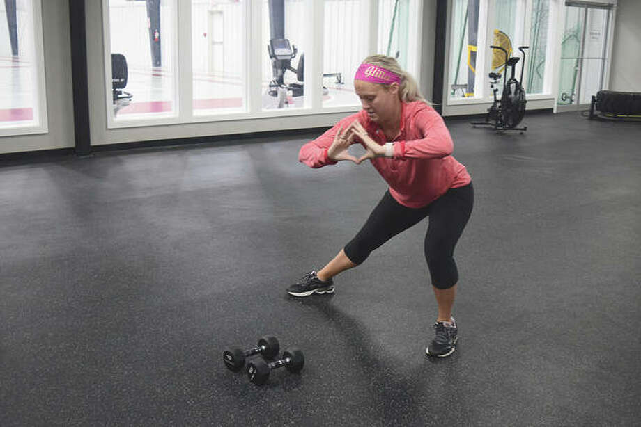 Jessica Rohn, owner of Fitness World Health Club & Sports Complex, stretches before a freeweight workout. Rohn and her staff host workouts on Facebook Live so members can still get in their exercising. Photo: Marco Cartolano | Journal-Courier