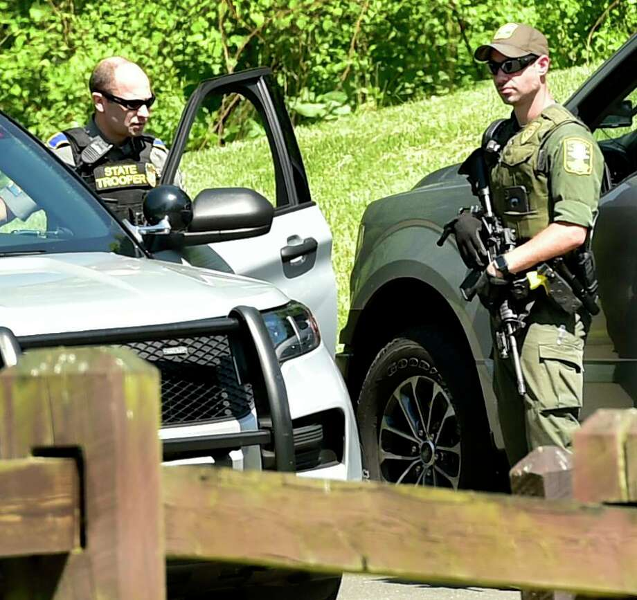 A Connecticut Department of Energy and Environmental Protection officer, right, talks with a state trooper Sunday during the search for suspected murderer Peter Manfredonia, 23, described as armed and dangerous Sunday morning at Osbornedale State Park in Derby after a stolen vehicle linked to the suspect was found on Hawthorne Avenue near Cullens Hill Road in Derby. The area borders Osbornedale State Park. The discovery launched an extensive search of the park and on local streets and in neighborhoods near Osbornedale and Roosevelt Drive where law enforcement secured another crime scene thought to be connected to Manfredonia. State Police said Manfredonia is believed to be armed with pistol and long guns. Manfredonia is wanted in a homicide and serious assault in northeastern Connecticut. Photo: Peter Hvizdak / Hearst Connecticut Media / New Haven Register
