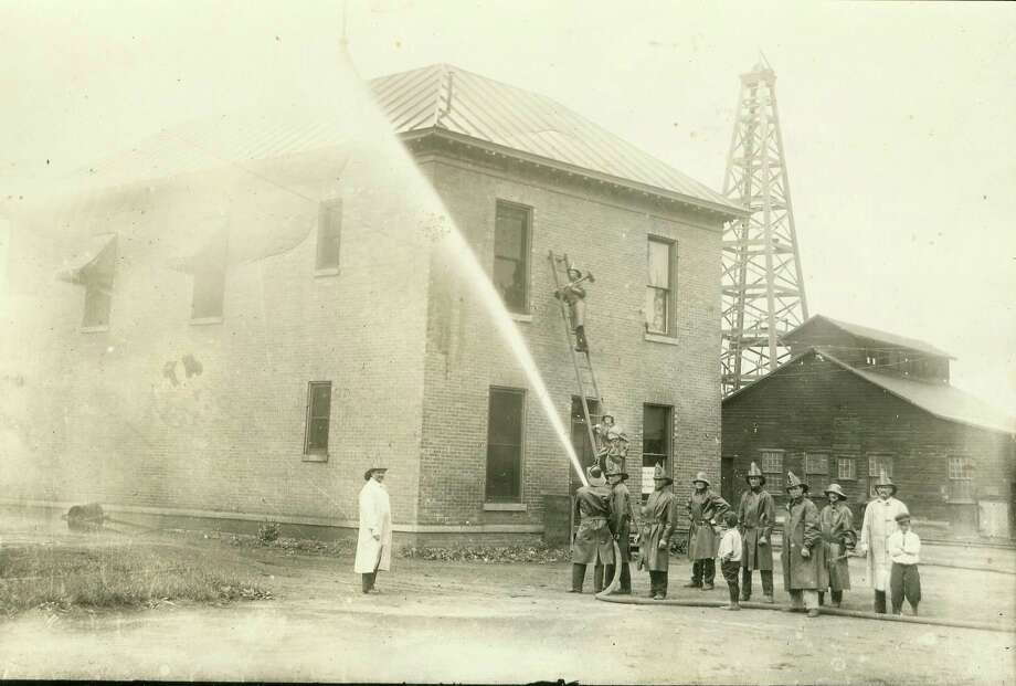 The Manistee Fire Department holds a firefighting drill in this early 1900 photograph.