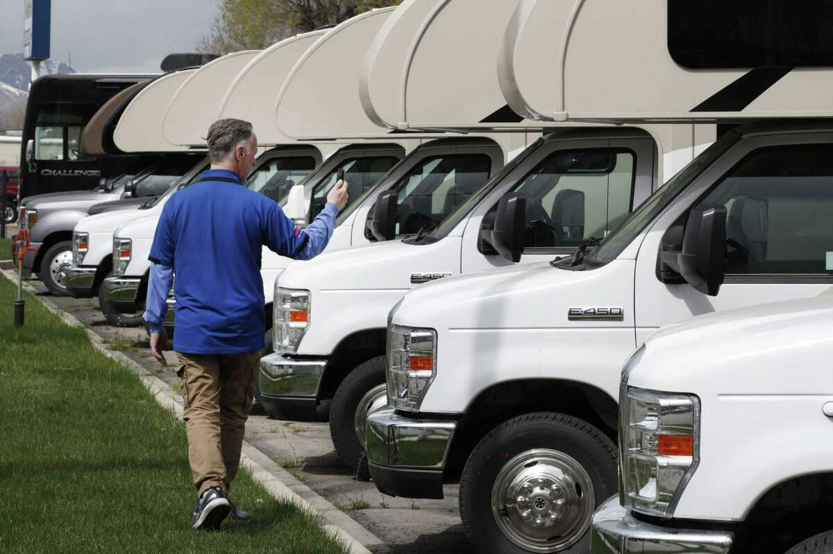 A salesperson shows potential customers RVs virtually, using his mobile phone, at tMotor Sportsland RV dealership in Salt Lake City on April 6.