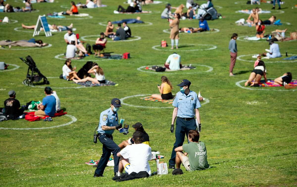 San Francisco police officer cadets distribute face masks to people at Dolores Park in San Francisco, California on May 22, 2020 amid the novel coronavirus pandemic.