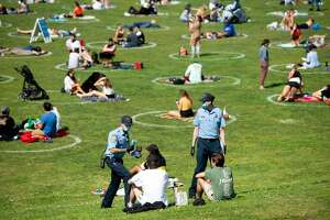 San Francisco police officer cadets distribute face masks to people at Dolores Park in San Francisco, California on May 22, 2020 amid the novel coronavirus pandemic. (Photo by Josh Edelson / AFP) (Photo by JOSH EDELSON/AFP via Getty Images)
