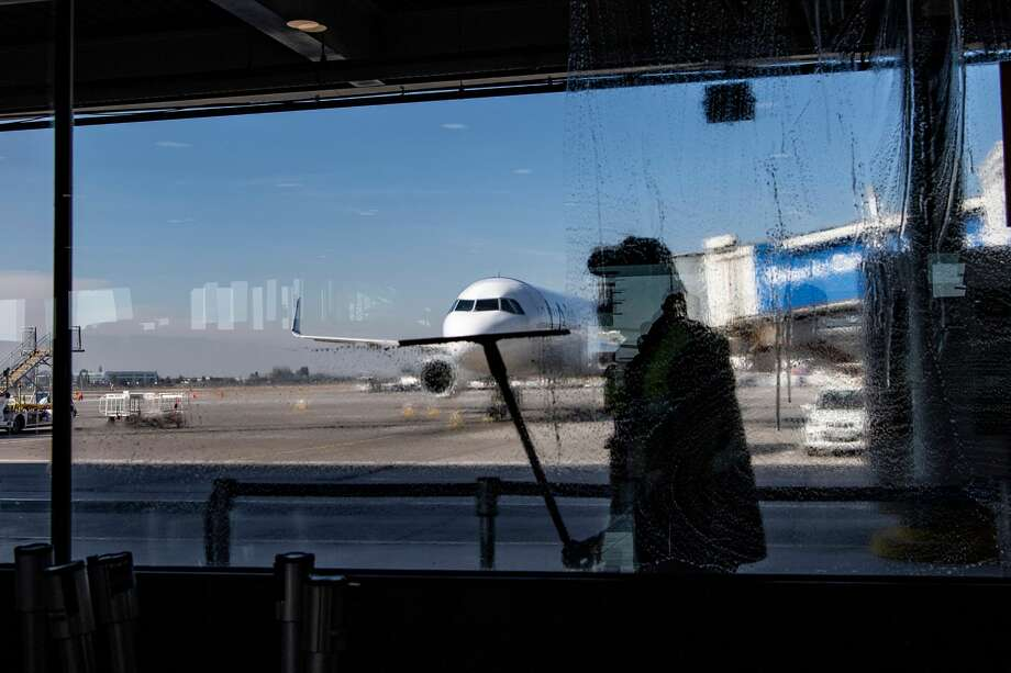 A worker cleans a window at Santiago International Airport, in Santiago, on April 20, 2020 during the new coronavirus, COVID-19, pandemic. - Latin America's biggest airline, the Brazilian-Chilean group LATAM, announced last Friday that the 95% reduction of its passenger operations announced in April will be extended until May due to the coronavirus crisis, which will cause a deeper impact than expected. (Photo by MARTIN BERNETTI / AFP) (Photo by MARTIN BERNETTI/AFP via Getty Images) Photo: MARTIN BERNETTI/AFP Via Getty Images