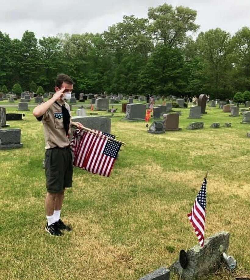 Tristen Kayfus, senior patrol leader with Troop 31, proudly honors a veteran after placing a flag at the grave. Photo: Courtesy Of Jim Ciaglo / Danbury News Times