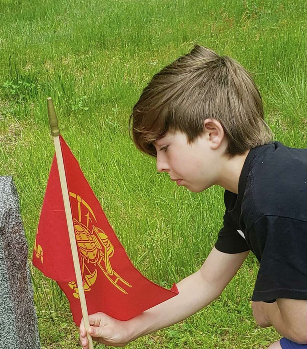 Quinn Carlson Parker, 10, and his family visited Northville Cemetery, where they placed flags at grave sites.