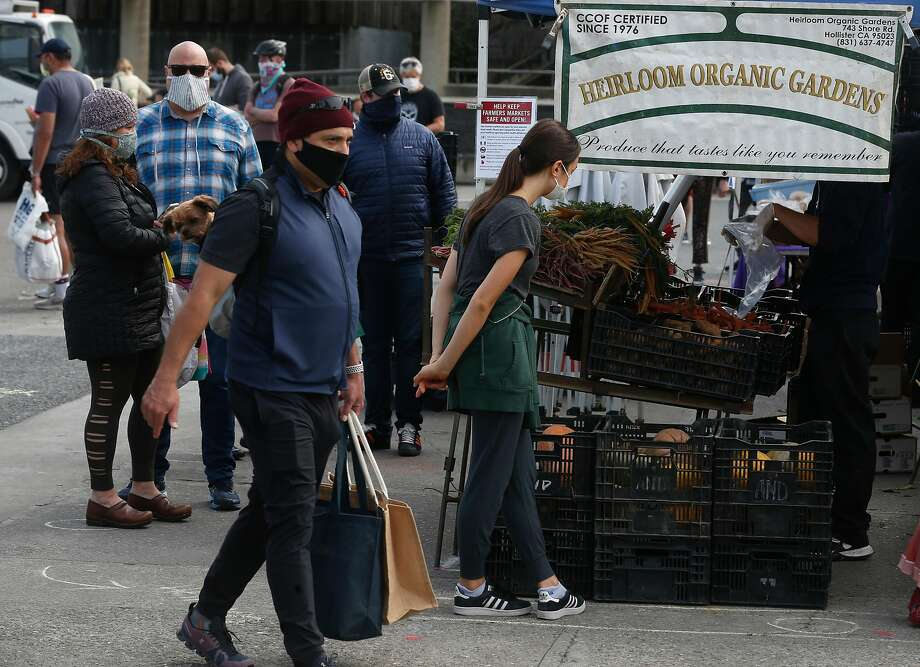 Customers and vendors wear face masks and maintain social distance at the Ferry Plaza Farmers Market in San Francisco. Photo: Paul Chinn / The Chronicle