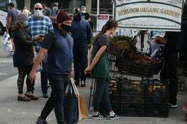 Customers and vendors wear face masks and maintain social distance at the Ferry Plaza Farmers' Market in San Francisco, Calif. on Saturday, May 2, 2020.
