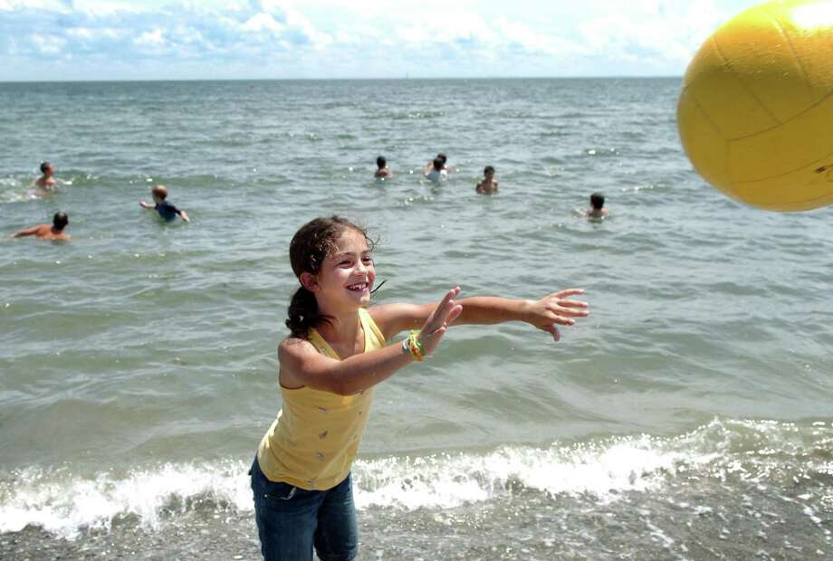 Nine-year-old Jensen Gutzwiller, of Westport, plays a game of monkey-in-the-middle while other Camp Compo campers stay cool in the water Friday July 9, 2010 at Compo Beach in Westport. Photo: Autumn Driscoll / ST / Connecticut Post