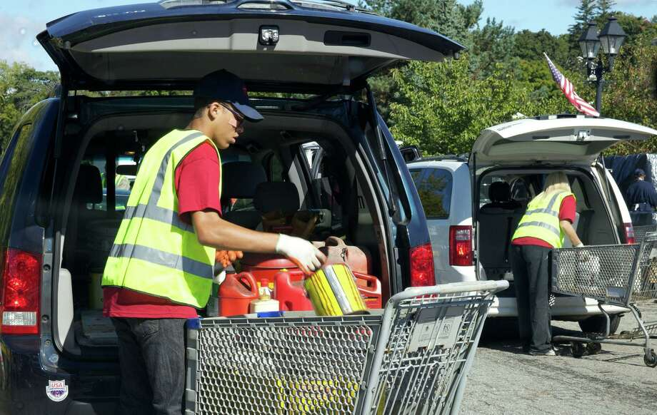 Items are removed from participating vehicles during a hazardous waste collection day in New Milford, Conn. Photo: Trish Haldin / The News-Times Freelance