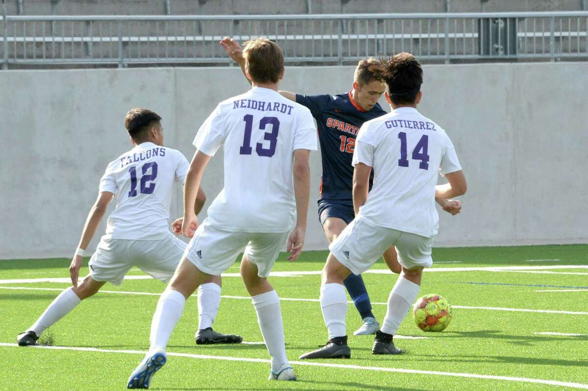 Thomas Murray (12) of Seven Lakes scores past 3 defenders during the first half of Region III Area Round soccer playoff match between the Seven Lakes Spartans and the Jersey Village Falcons on Tuesday, April 2, 2019 at Legacy Stadium, Katy, TX.