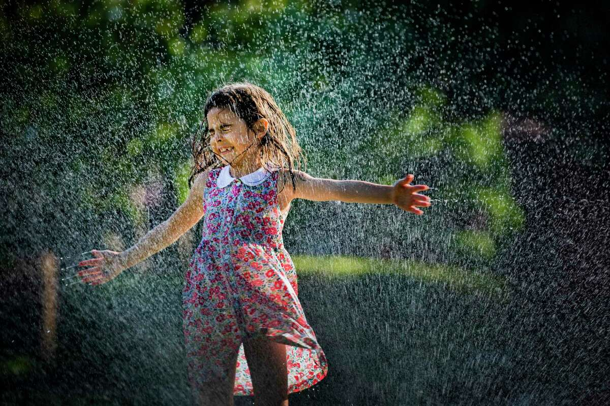 Penelope Eslick, 7, enjoys the water from sprinklers during a walk with her father at Sunset Boulevard near the University Place community in Houston Wednesday, May 20, 2020.