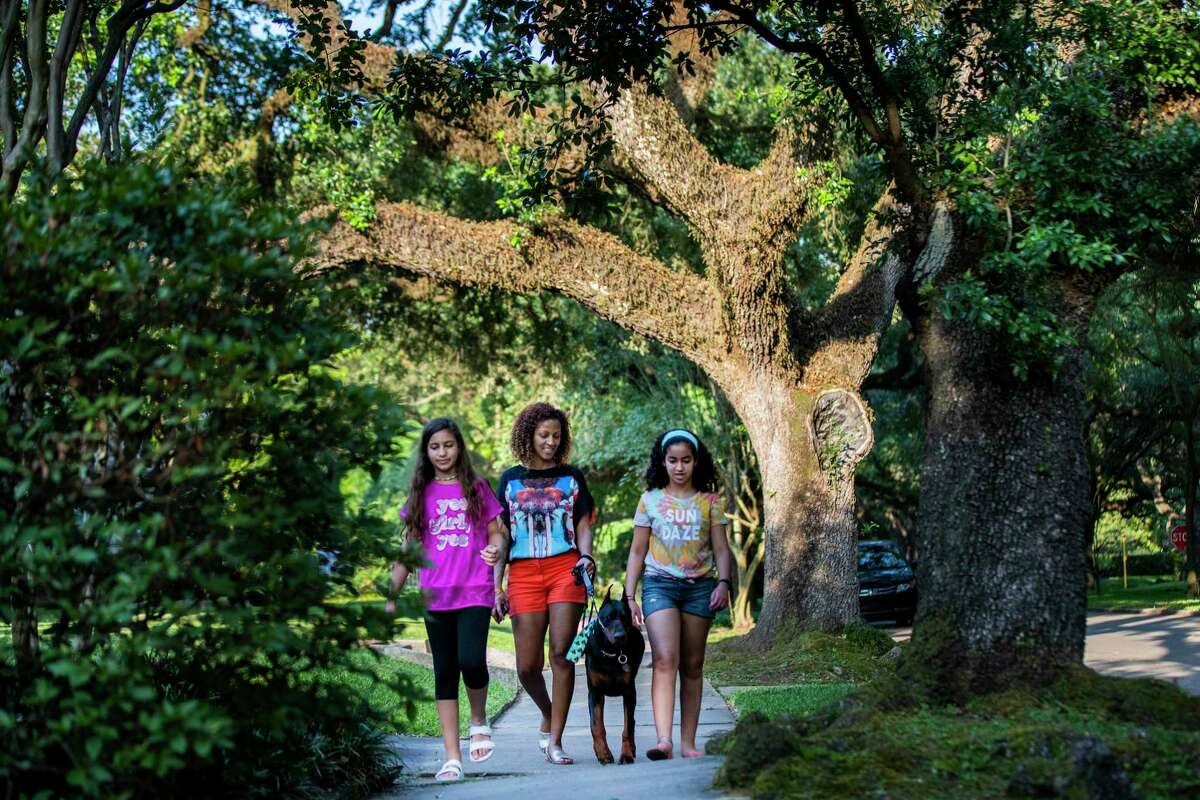 Monique Kaufman, 43, walks the family pet Melech with her daughters Vivian Kaufman, 10, and Laurel Kaufman, 13, at Sunset Boulevard near the University Place community in Houston on Wednesday, May 20, 2020.
