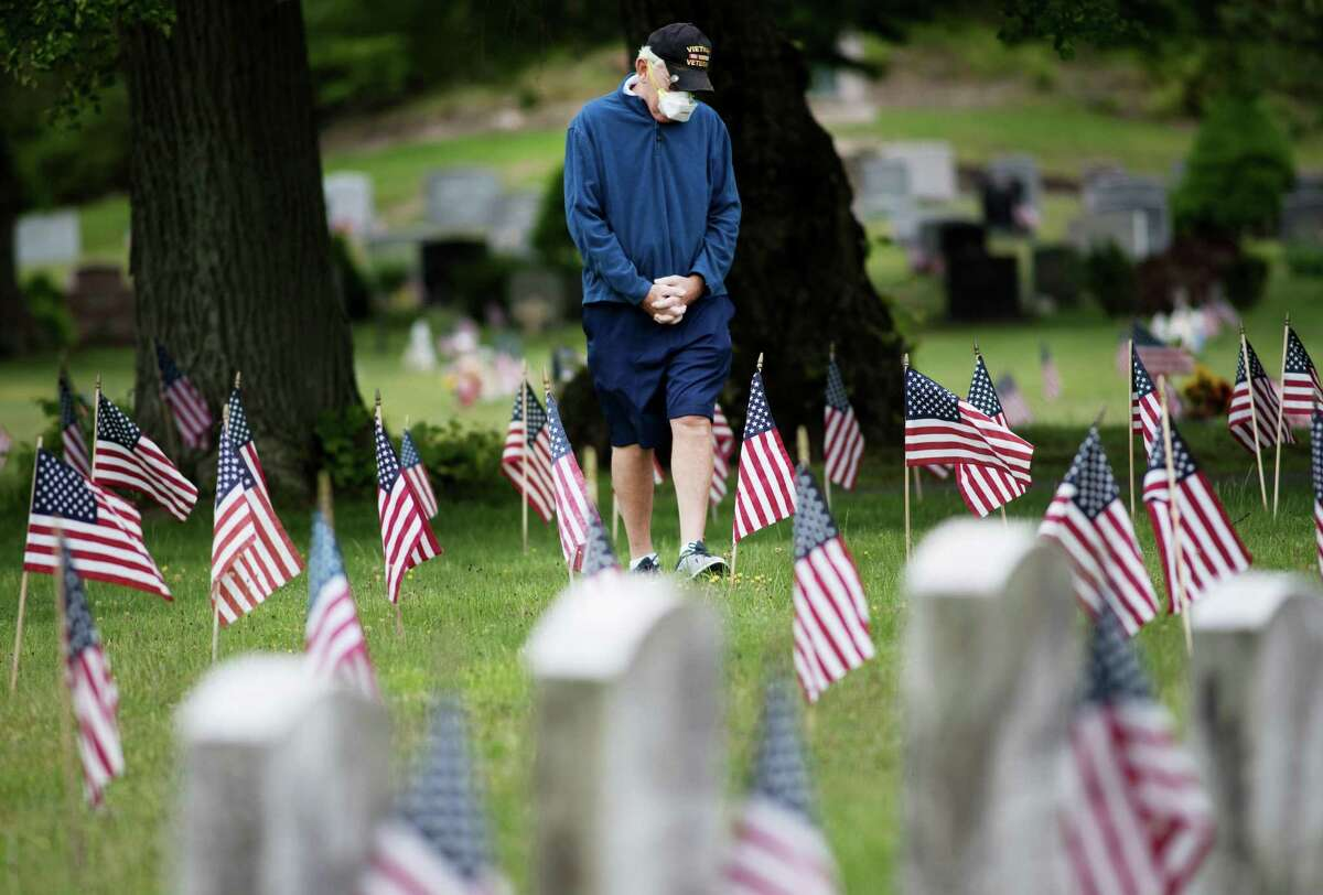An unknown visitor observes Darien's Memorial Day ceremony from a distance on Monday, May 25.