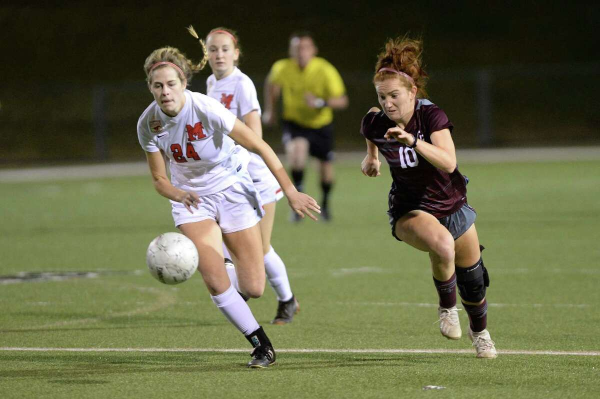 Reagan Goodwine (24) of Memorial and Abby McCain (10) of Cinco Ranch chase a loose ball during the first half of Region III Area Round soccer playoff match between the Cinco Ranch Cougars and the Memorial Mustangs on Tuesday, April 2, 2019 at Rhodes Stadium, Katy, TX.