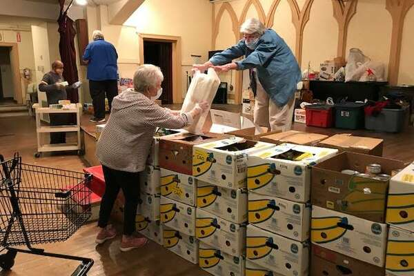 Sister Mary Ellen hands box lunch containers to volunteer Martha White in preparation for a soup kitchen lunch at Sacred Heart Church.