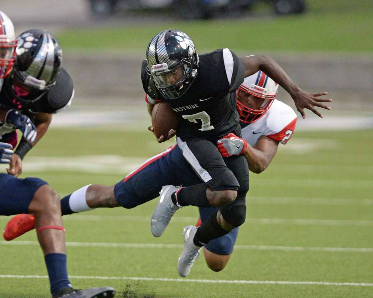 Akeem Benjamin (7) of Westside is tackled by Oliver Jack (25) of Lamar on a quarterback keeper during the first quarter of a 6A Region III District 18 football game between the Lamar Texans and the Westside Wolves on Friday, October 4, 2019 at Delmar Stadium, Houston, TX.