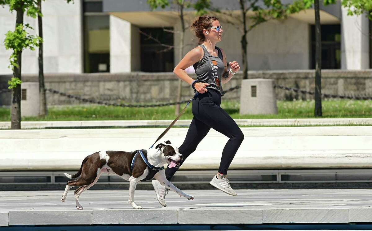 A woman runs with her dog at the Empire State Plaza on Tuesday, May 26, 2020 in Albany, N.Y. (Lori Van Buren/Times Union)