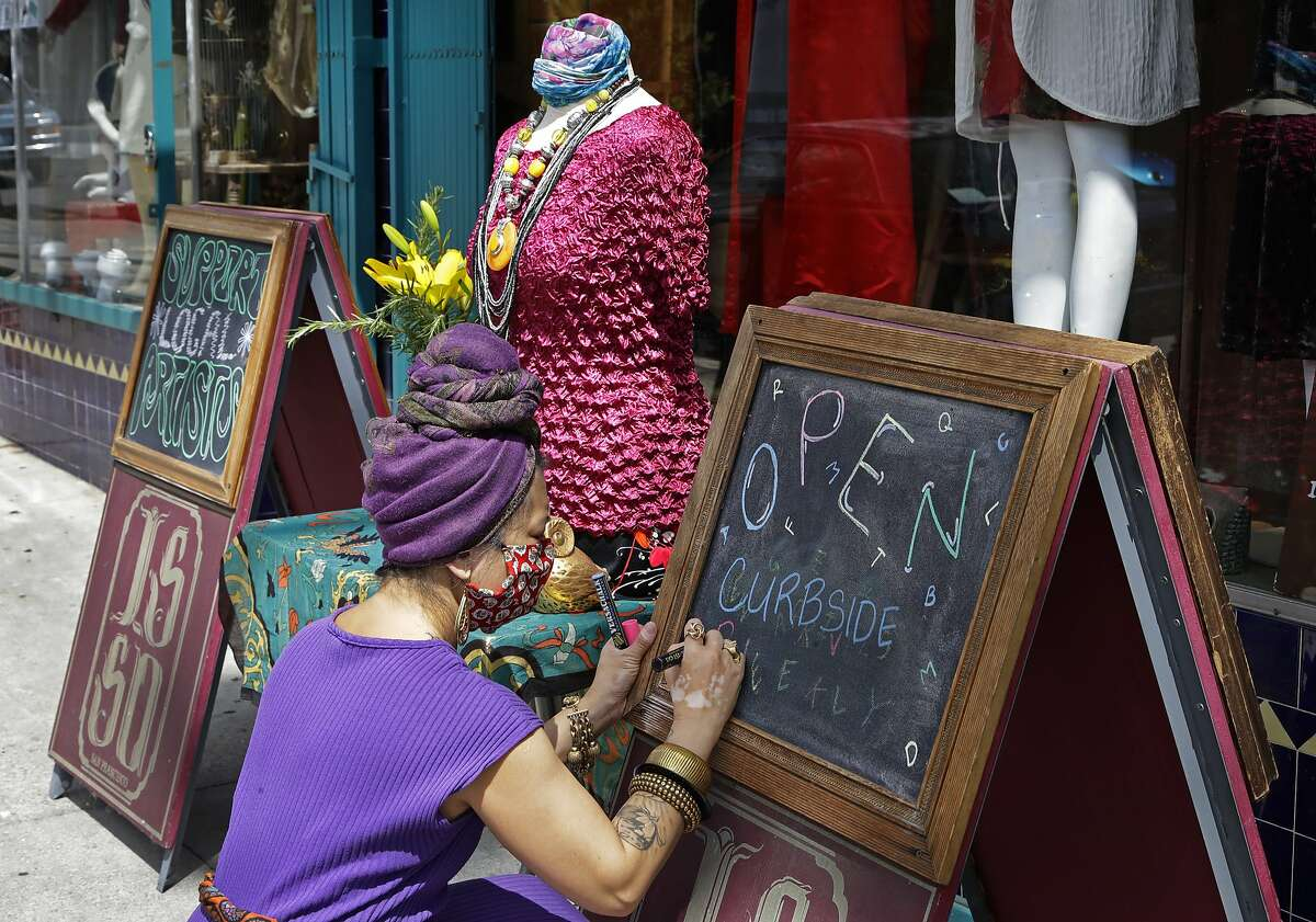 Marie Biscarra, co-owner of ISSO fashion boutique, finishes writing a sign declaring her business open for curbside delivery on Monday, May 18, 2020, in San Francisco. A San Francisco Bay Area county that reported the first known death from coronavirus in the U.S. says it will allow some retail businesses to re-open, although it's not known when. Santa Clara County said Monday in a joint statement with four other counties that COVID-19 trends were looking positive enough to allow curbside and storefront shopping. The statement says the trend of new cases and the number of hospitalized patients is stable or declining. San Francisco, Marin and San Mateo counties started allowing some retail sales Monday. (AP Photo/Ben Margot)