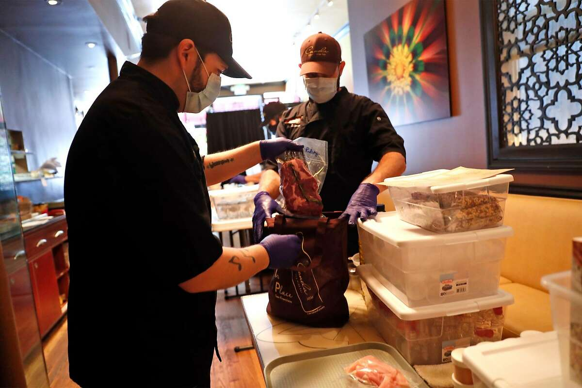 Canela's Chris Munoz (left) and chef Mat Schuster construct a butcher bag at the restaurant on Market Street in San Francisco, Calif., on Sunday, May 24, 2020.