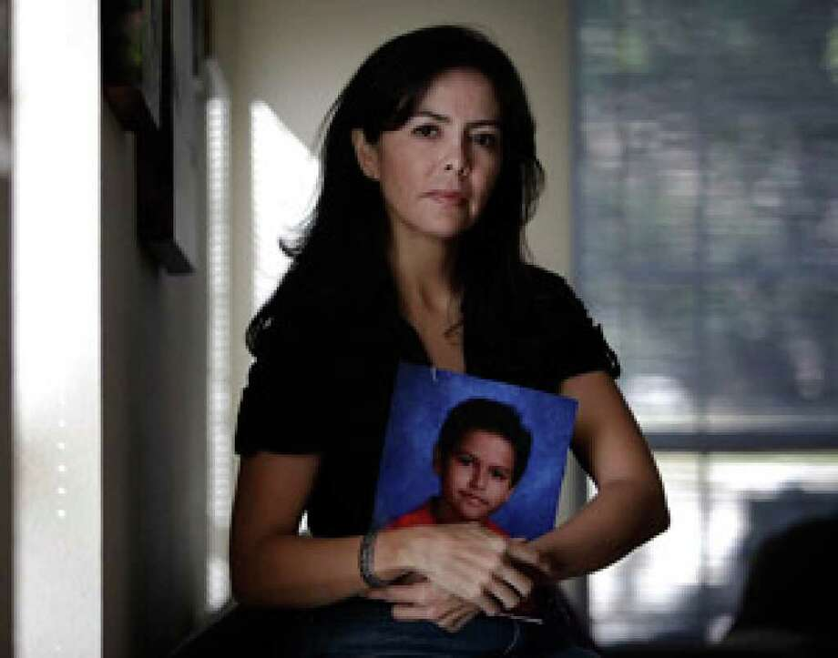Berenice Diaz holds a photo of her son, Jean Paul Lacombe.