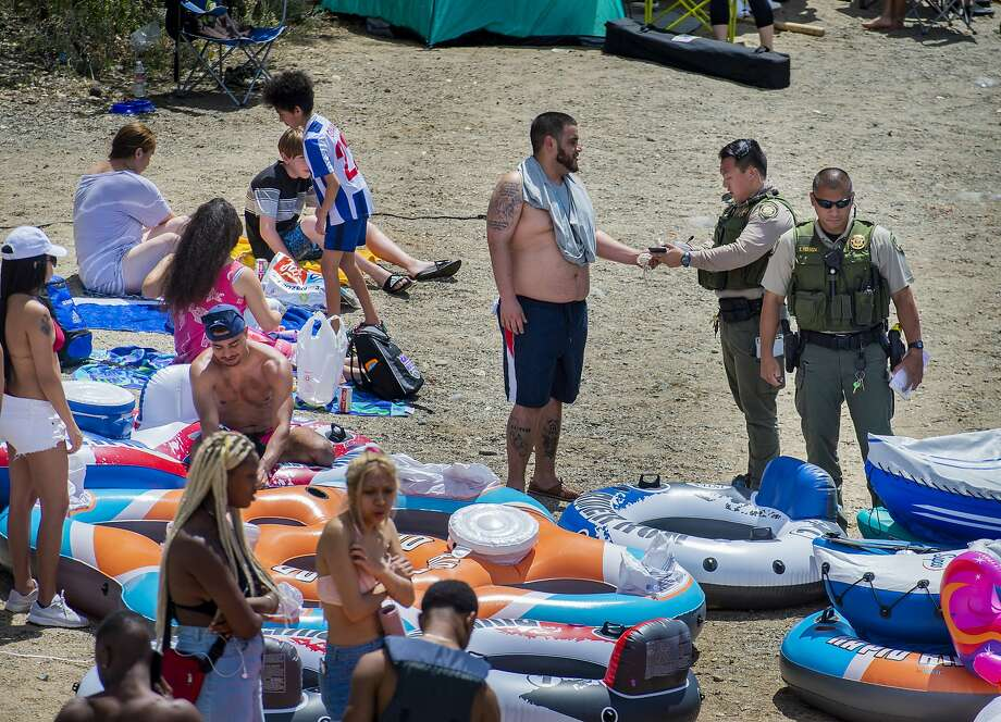 A Sacramento County park ranger issues an alcohol citation to an American River visitor in the Sunrise Recreation Area near Rancho Cordova, Calif., during the Memorial Day weekend, Sunday, May 24, 2020. Alcohol is banned along the shoreline of the river between Hazel and Watt avenues on Memorial Day weekend, the Fourth of July and Labor Day weekend. (Daniel Kim/The Sacramento Bee via AP) Photo: Daniel Kim, Associated Press