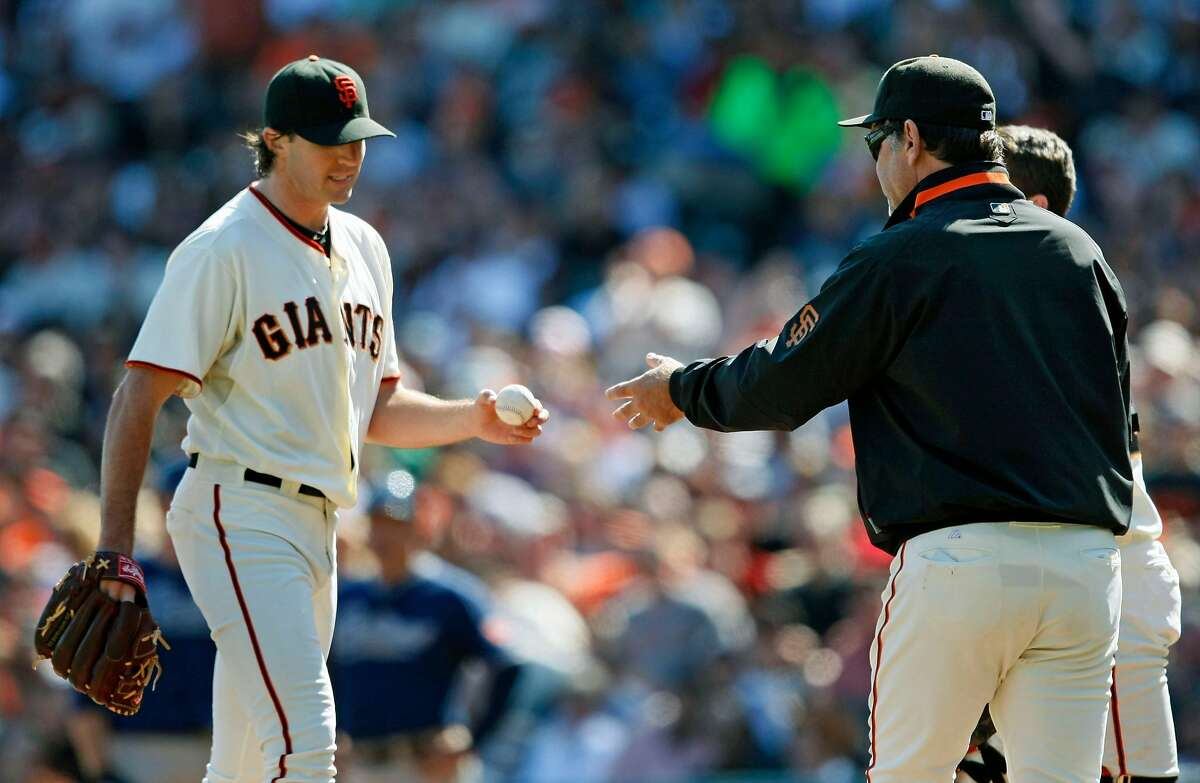 San Francisco Giants' Barry Zito who gave up four runs early into their game with the San Diego Padres hands over the ball to manager Bruce Bochy, right Saturday, Oct. 2, 2010, in San Francisco.