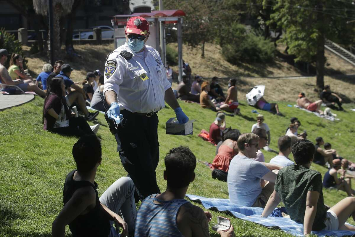 San Francisco Police Auxiliary Law Enforcement Response Team (ALERT) volunteer David Flynn offers face masks to help prevent the spread of the coronavirus at Dolores Park in San Francisco, Sunday, May 24, 2020.