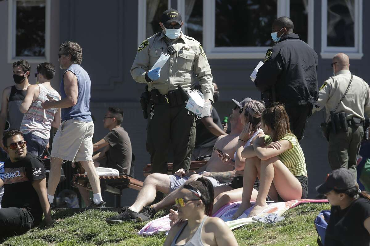 A San Francisco Sheriff's officer hands out face masks to help prevent the spread of the coronavirus at Dolores Park in San Francisco, Sunday, May 24, 2020.