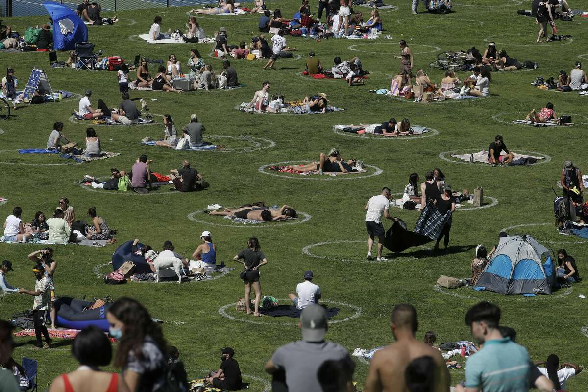 Visitors set up inside circles designed to help prevent the spread of the coronavirus by encouraging social distancing at Dolores Park in San Francisco, Sunday, May 24, 2020.