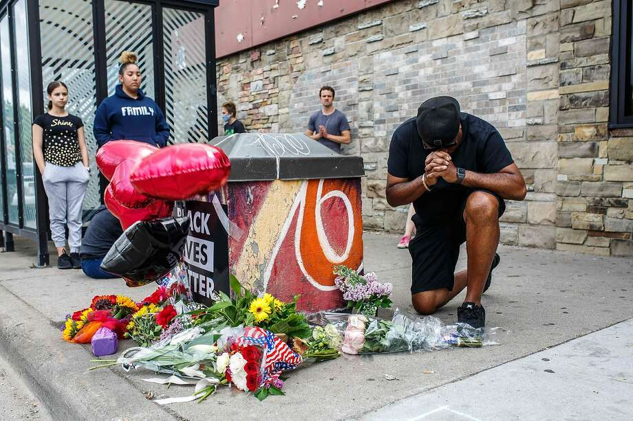 A protester prays in front of the memorial of George Floyd who died in custody on May 26, 2020 in Minneapolis, Minnesota.� - An FBI investigation is underway following a fatal encounter May 25, 2020 between Minneapolis police and an unarmed black man. In a statement early Tuesday, police said the man had a medical incident during an attempted arrest. However, video of the encounter shows an officer with his knee on the mans neck for at least seven minutes. Before the man loses consciousness, he repeatedly tells officers that he cant breathe. (Photo by Kerem Yucel / AFP) (Photo by KEREM YUCEL/AFP via Getty Images) Photo: Kerem Yucel, AFP Via Getty Images