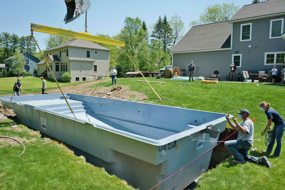 Employees of Concord Pools and Spas, Danny Connors, background left, Jon Connors, background second from left, Brent Hanson, foreground second from right, and Sam Pellerin, foreground right, install an inground pool at a home on Tuesday, May 26, 2020, in Wilton, N.Y. (Paul Buckowski/Times Union)