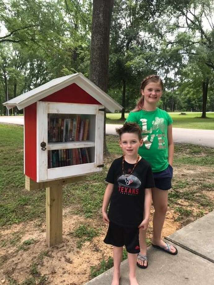 The grandchildren of Paul and Celia Hogan stand beside a little library the Hogans installed at the end of their driveway in the Bridgepoint subdivision. Celia Hogan wanted to share books she collected with her neighbors. Photo: Courtesy Photo