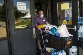 Bob Wallace pushes a cart towards a vehicle while volunteering at a donation drive providing residents affected by flooding with toiletries, cleaning supplies, food items, toys, pet supplies and much more at Meridian Elementary Tuesday, May 26, 2020. (Katy Kildee/kkildee@mdn.net)