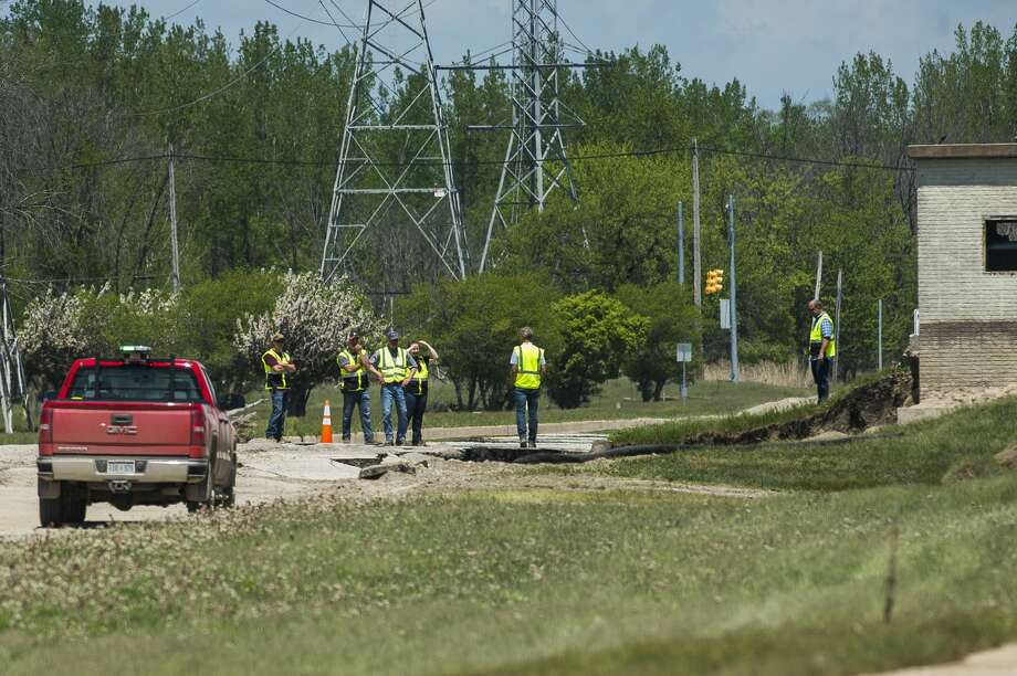 Workers assess the damage sustained to Poseyville Road Tuesday, May 26, 2020. (Katy Kildee/kkildee@mdn.net) Photo: (Katy Kildee/kkildee@mdn.net)
