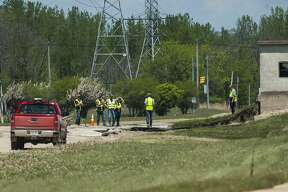 Workers assess the damage sustained to Poseyville Road Tuesday, May 26, 2020. (Katy Kildee/kkildee@mdn.net)