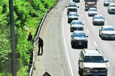 Traffic crawls by as Stamford Police officers continue to search the embankment adjacent to I-95 Northbound in and around the area of the Fairfield Avenue overpass following a reported shooting incident on May 26, 2020. A person of interest was taken by police and EMS to Stamford Hospital for evaluation after being pick up on I-95 northbound attempting to wave down traffic near Fairfield Avenue. The investigation is ongoing.