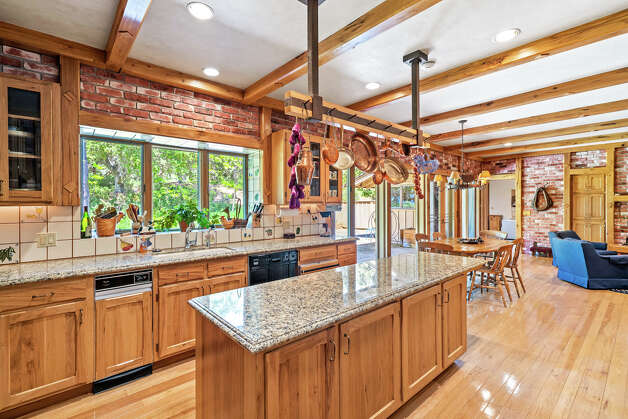 """The property features seven separate dwellings, but at its heart is a luxurious 5,000-square-foot, ranch-style home with one bedroom, one bath, and two half baths. """"The main owner's home was rebuilt,"""" said McDavid. """"It started as a remodel of the kitchen, and that blossomed into a rebuild of the home."""" A covered walkway connects the main home to a two-bedroom guest wing. There's also a separate two-bedroom guest cottage. Photo: Courtesy Hall And Hall"""
