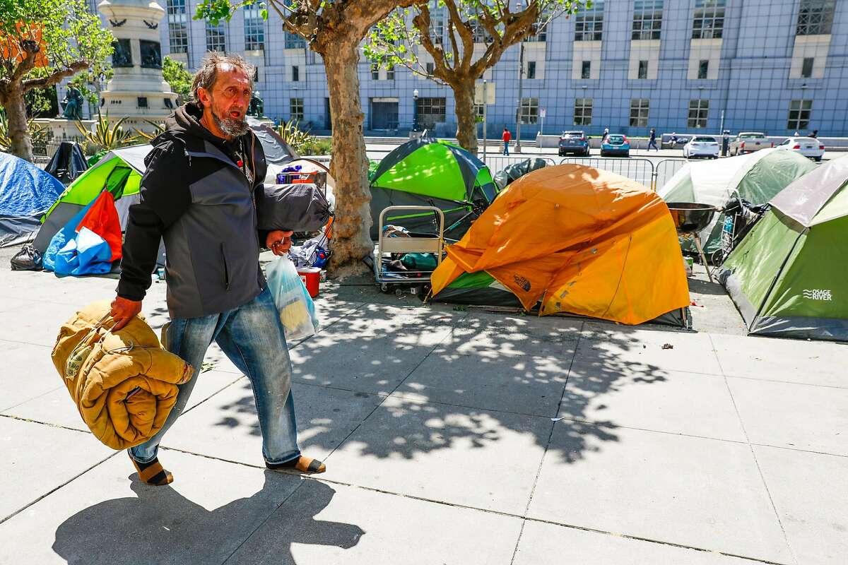 Homeless man Larry Gaspar walks by an encampment on Fulton Street on Wednesday, May 6, 2020 in San Francisco, California.