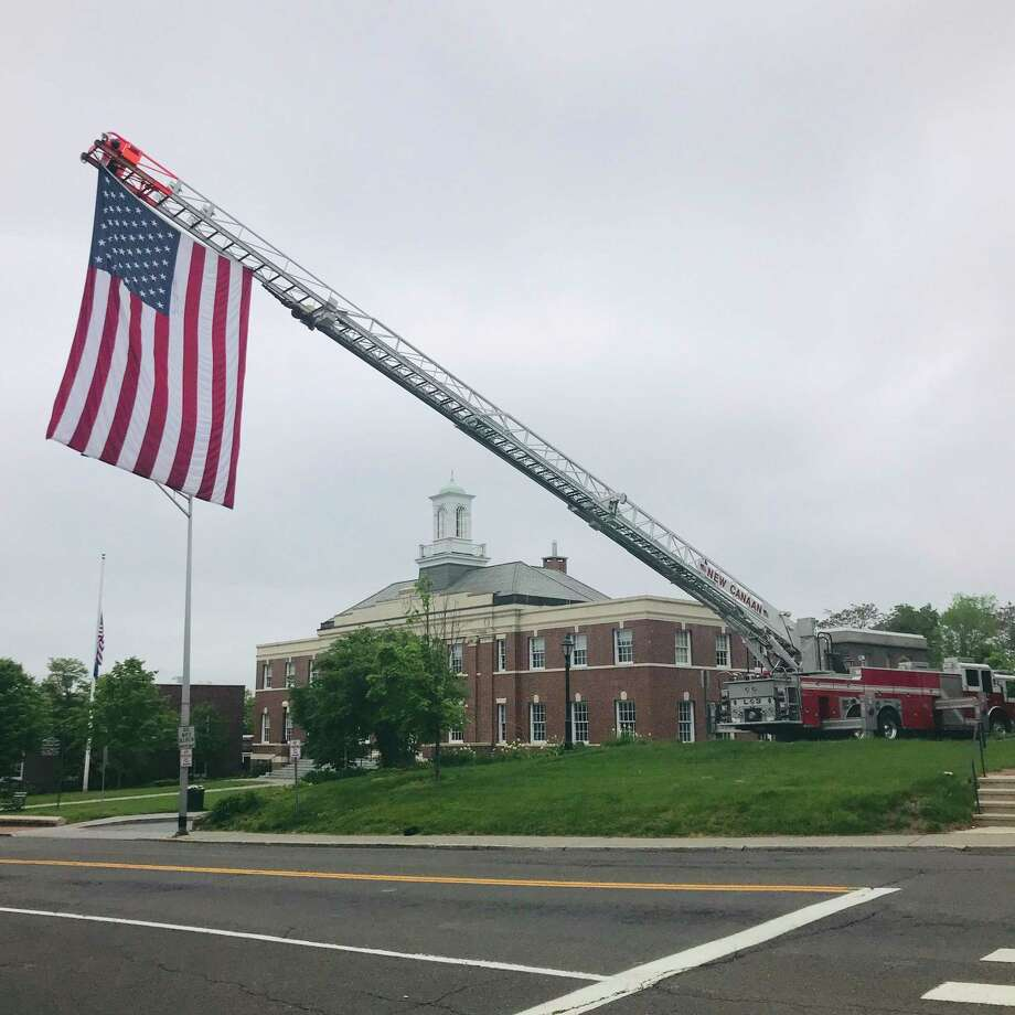 The American flag hangs over Main Street from the New Canaan Fire Department's Ladder 3 on Memorial Day. There was no parade or public ceremony, but New Canaan recognized the fallen in a smaller gathering that was broadcast. Photo: Meredith Bach / Contributed Photo / New Canaan Advertiser Contributed